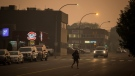 A woman walks across a street just after 10 a.m. in near darkness due to thick smoke blanketing the city because of wildfires in the region, in Prince George, B.C., on Friday, August 17, 2018. THE CANADIAN PRESS/Darryl Dyck