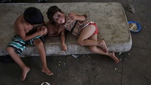 In this March 8, 2018 photo, children rest on a mattress inside the Tancredo Neves Gymnasium that is operating as a shelter for Venezuelans in Boa Vista, Roraima state, Brazil. (AP Photo/Eraldo Peres)