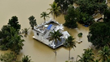 A house is partially submerged in flood waters in Chengannur in the southern state of Kerala, India, Sunday, Aug.19, 2018. Some 800,000 people have been displaced and over 350 have died in the worst flooding in a century. (AP Photo)