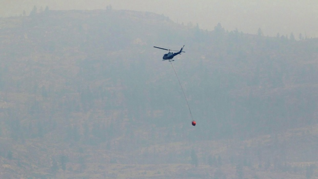 A helicopter battles a wildfire along the shore line of Highway 97 heading towards Summerland B.C. on Thursday July 18,2018. THE CANADIAN PRESS/Jeff Bassett