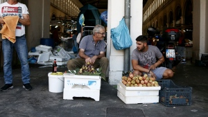 Two street vendors talk each other outside the main fish market of Athens, Monday, Aug. 20, 2018, on the day that Greece's eight-year crisis will be officially over. (Panayiotis Tzamaros / InTime News via AP)
