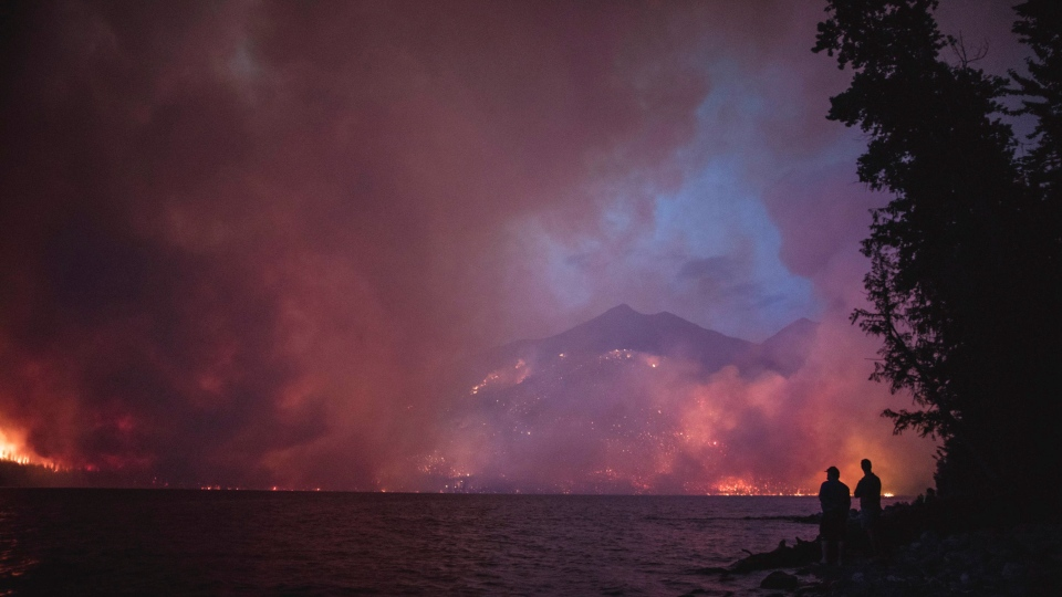 This Sunday, Aug. 12, 2018 file photo provided by the National Park Service shows the Howe Ridge Fire from across Lake McDonald in Glacier National Park, Mont. (National Park Service via AP)