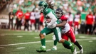 Saskatchewan Roughriders running back Tre Mason (10) runs the ball under pressure from the Calgary Stampeders defence during first half CFL action in Regina on Sunday, August 19, 2018. THE CANADIAN PRESS/Matt Smith.
