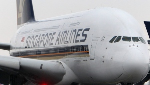 An airport vehicle passes a Singapore Airlines Airbus A380 aircraft parked on the tarmac at the international airport in Frankfurt, Germany, Friday, Feb. 17, 2012. (Michael Probst / The Associated Press)