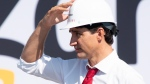 Prime Minister Justin Trudeau adjusts his hat as he participates in a ground breaking ceremony for an Amazon distribution centre in Ottawa, Monday, Aug. 20, 2018. (Adrian Wyld / THE CANADIAN PRESS)