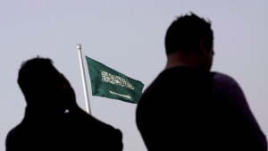 People pray at an open air makeshift mosque in front of a giant Saudi Flag in Jiddah, Saudi Arabia, Wednesday, June 21, 2017. A Nova Scotia health official says the pending departure of 59 Saudi Arabian medical residents will result in surgical delays over the coming months. THE CANADIAN PRESS/AP, Amr Nabil