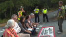 RCMP officers watch on as a group of pipeline protesters block the entrance to a Kinder Morgan terminal in Burnaby, B.C.