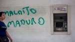 """A wall is spray painted with a message that reads in Spanish: """"Damn Maduro"""" next to an ATM machine in Caracas, Venezuela, Monday, Aug. 20, 2018. Banks remained closed Monday as they prepare to release the """"sovereign bolivar,"""" the new currency printed with five fewer zeroes in a bid to tame soaring inflation. (AP Photo/Ariana Cubillos)"""