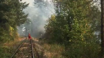 A still image from West Vancouver Fire Department video shows a firefighter monitoring a blaze on Monday, Aug. 20, 2018.