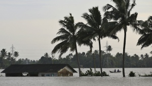 Two men row a boat through a flooded paddy field next to an inundated structure in Alappuzha in the southern state of Kerala, India, Monday, Aug. 20, 2018. (AP Photo/Aijaz Rahi)