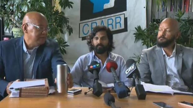 Julian Menezes (centre) speaks to the media about his settlement
