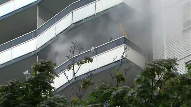 Smoke billows from the balcony of a highrise apartment unit in St. James Town on August 21, 2018.