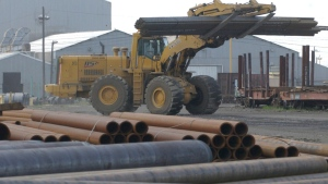 Pipe is relocated with a large front-end loader at one of the Texas pipe yards in a photo from Wednesday, June 25, 2003. (AP Photo/The Longview News-Journal, Kevin Green)