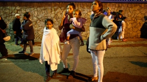 """Residents stand outside their apartments in a street near the """"Tower of David"""" skyscraper, which suffered an inclination after a powerful earthquake shook eastern Venezuela, causing buildings to be evacuated in the capital of Caracas, Venezuela, Tuesday, Aug. 21, 2018.  (AP Photo/Ariana Cubillos)"""