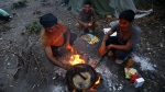 Migrants prepare dinner in a makeshift migrant camp in Bihac, 450 kilometres northwest of Sarajevo, Bosnia on on Tuesday, Aug. 14, 2018. (AP Photo/Amel Emric)