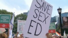 A person holding a sign protesting the repeal of the sex-education curriculum is seen.