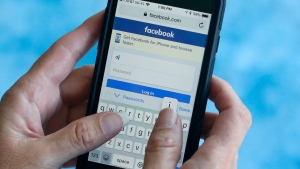 In this file photo dated Tuesday, Aug. 21, 2018, a Facebook start page is shown on a smartphone in Surfside, Fla. USA. (AP Photo/Wilfredo Lee)