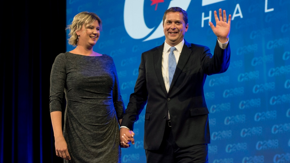 Conservative leader Andrew Scheer and his wife Jill Scheer arrive on stage at the party's national convention in Halifax on Thursday, Aug. 23, 2018. (Darren Calabrese / THE CANADIAN PRESS)