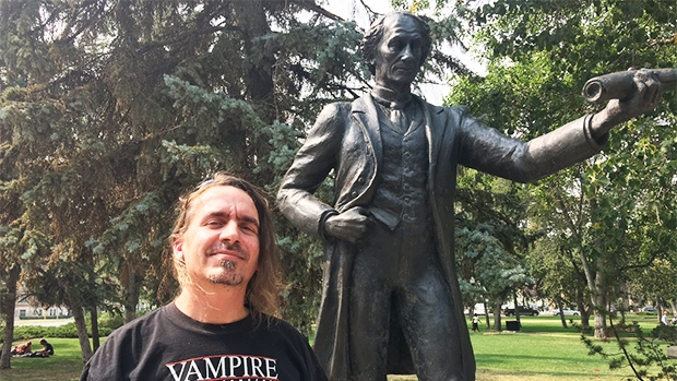 Patrick Johnson poses with the statue of John A. Macdonald in Victoria Park in Regina. (CREESON AGECOUTAY/CTV REGINA)