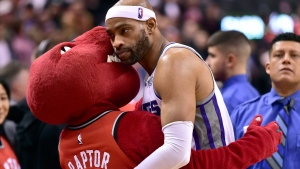 In this file photo, Vince Carter (15), then the Sacramento Kings guard, embraces The Raptor, the Toronto Raptors mascot during second half NBA basketball action in Toronto on Sunday, December 17, 2017. (THE CANADIAN PRESS/Frank Gunn)