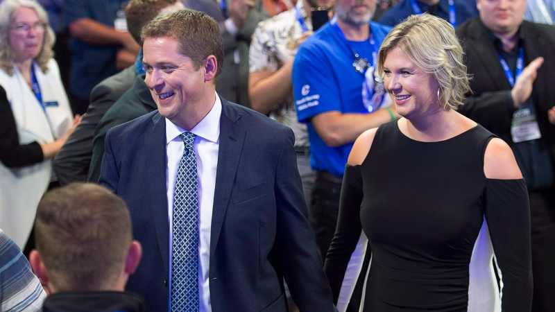 Conservative Party of Canada Leader Andrew Scheer and his wife Jill head through the crowd as he prepares to address the party's national policy convention in Halifax on Friday, Aug. 24, 2018. THE CANADIAN PRESS/Andrew Vaughan