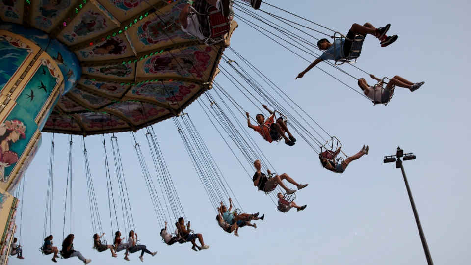 Children swing on a midway ride at the 140th annual Canadian National Exhibition in Toronto on Sunday, August 19, 2018. THE CANADIAN PRESS/Cole Burston