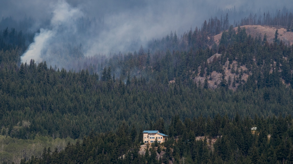 The Shovel Lake wildfire burns on a mountain behind a home near Fort Fraser, B.C., on Thursday August 23, 2018. THE CANADIAN PRESS/Darryl Dyck