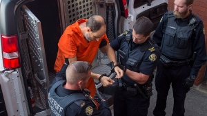 Matthew Vincent Raymond, charged with four counts of first degree murder, arrives at provincial court in Fredericton on Monday, Aug. 27, 2018. Two city police officers were among four people who died in a shooting in a residential area on the city's north side. THE CANADIAN PRESS/Andrew Vaughan