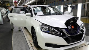 A worker inspects a Nissan Sylphy Zero Emission, Nissan's first all-electric vehicle built in China, at a production line in Guangzhou, Guangdong province, China, Monday, Aug. 27, 2018. (AP Photo/Vincent Yu)