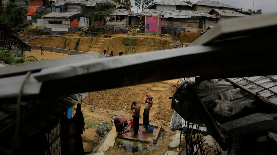 Rohingya refugees bathe at a hand water pump at Balukhali Refugee Camp in Bangladesh, Monday, Aug. 27, 2018.(AP Photo/Altaf Qadri)