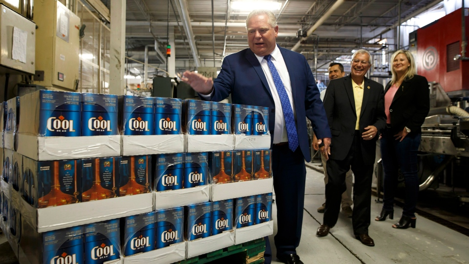 Premier Doug Ford slaps the top of boxes of beer as Finance Minister Vic Fedeli laughs in background at a brewery in Etobicoke, Ont. on Monday, Aug. 27, 2018. THE CANADIAN PRESS/Cole Burston