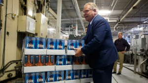 Ontario Premier Doug Ford holds a case of beer during a photo opportunity at a brewery in Etobicoke, Ont. on Monday, Aug. 27, 2018.  (THE CANADIAN PRESS/Cole Burston)