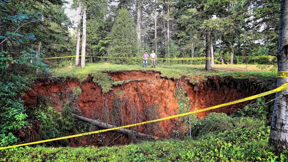Men look at a sinkhole in Oxford, N.S. on Aug.23, 2018 in a handout photo. A Nova Scotia town is urging the public to take caution as officials scramble to assess the massive, expanding sinkhole that has sucked up surrounding trees and picnic tables. (THE CANADIAN PRESS/HO-Sean Whalen Photography)