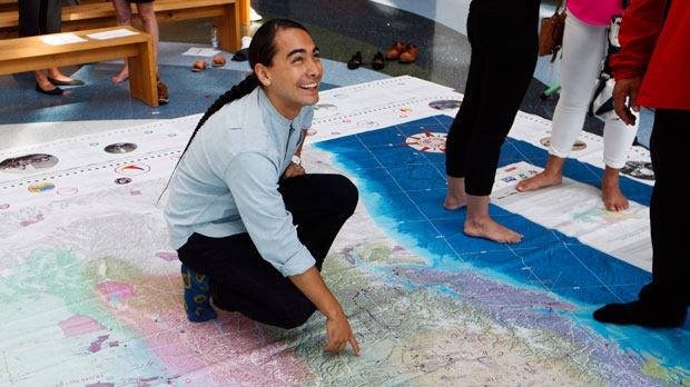 Julian Brave NoiseCat, a member of the Canim Lake Band, and a contributing editor of the newly unveiled Indigenous Peoples Atlas of Canada, points on a giant map at a launch event in Toronto, Wednesday August 29, 2018. The Indigenous Peoples Atlas of Canada includes a four volume print atlas, an online atlas, an app, and a giant floor map. (THE CANADIAN PRESS/Mark Blinch)