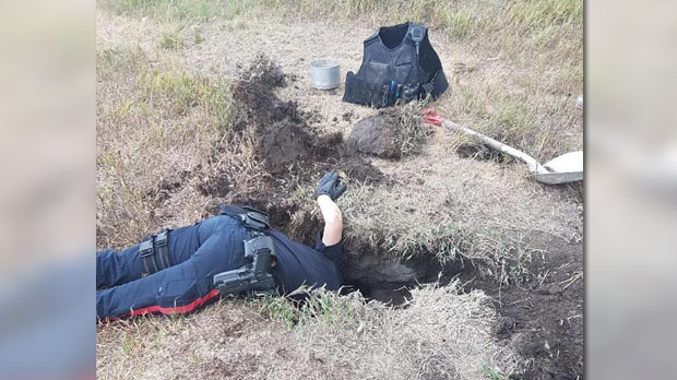 The department shared this photo of an officer reaching deeply, his head swallowed by the ground. (Facebook/Rivers Police Service)