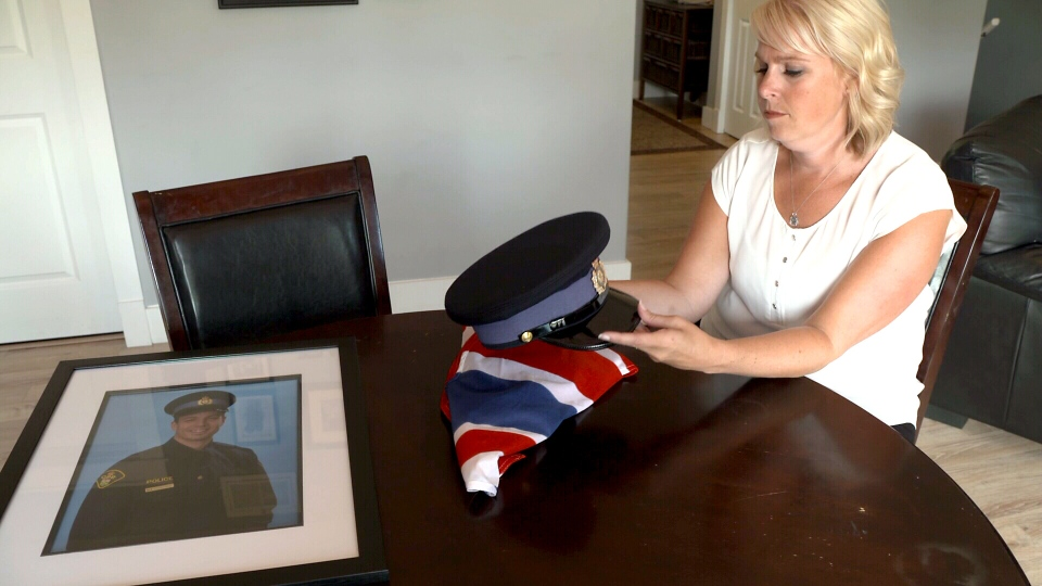 Sarah Routhier holds part of her late husband's OPP uniform.  OPP Sgt. Sylvain Joseph Francois Routhier was one of three officers in the force who took their own lives over a three-week time period.