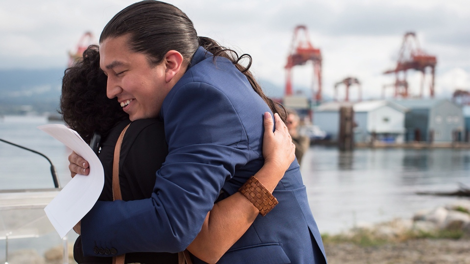 Khelsilem (Dustin Rivers), right, elected councillor and spokesperson for Squamish Nation, embraces Tsleil-Waututh Nation councillor Charlene Aleck in celebration before First Nations leaders respond to a Federal Court of Appeal ruling on the Kinder Morgan Trans Mountain Pipeline expansion, during a news conference in Vancouver on Thursday, Aug. 30, 2018. (THE CANADIAN PRESS/Darryl Dyck)