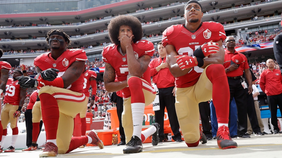 In this Oct. 2, 2016 file photo, from left, San Francisco 49ers outside linebacker Eli Harold, quarterback Colin Kaepernick and safety Eric Reid kneel during the national anthem before an NFL football game against the Dallas Cowboys in Santa Clara, Calif. (AP Photo/Marcio Jose Sanchez)