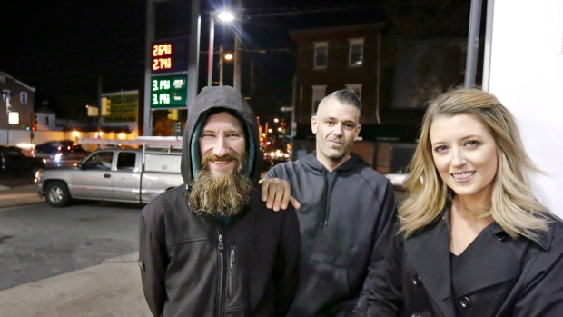In this Nov. 17, 2017, file photo, Johnny Bobbitt Jr., left, Kate McClure, right, and McClure's boyfriend Mark D'Amico pose at a Citgo station in Philadelphia. (Elizabeth Robertson/The Philadelphia Inquirer via AP)