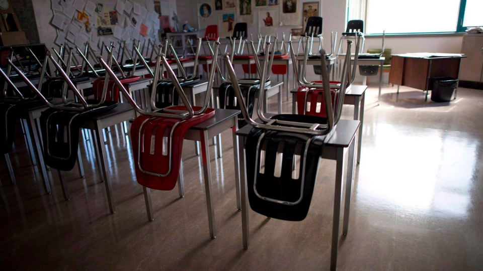 A vacant desksa are pictured at the front of a empty classroom is pictured at McGee Secondary school in Vancouver on Sept. 5, 2014. School districts in British Columbia are scrambling to hire an unprecedented number of teachers ahead of the new school year to adhere to reinstated class size standards. (Jonathan Hayward/The Canadian Press)