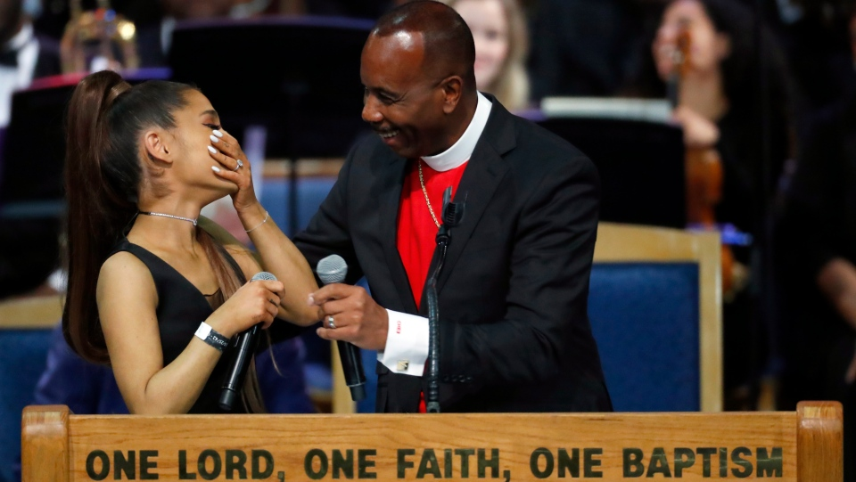 Ariana Grande, left, laughs with Bishop Charles H. Ellis during the funeral service for Aretha Franklin at Greater Grace Temple, Friday, Aug. 31, 2018, in Detroit. (AP Photo/Paul Sancya)
