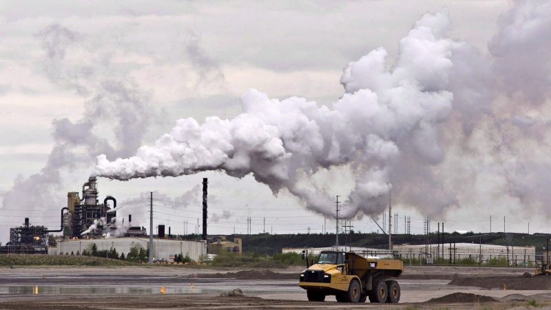 A dump truck works by an oilsands extraction facility near the city of Fort McMurray, Alberta on Sunday June 1, 2014. (THE CANADIAN PRESS/Jason Franson)