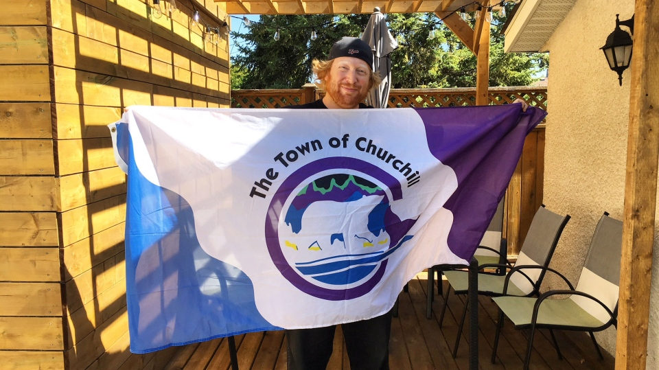 Joe Stover poses with the Town of Churchill flag. (Source: Beth Macdonell/ CTV Winnipeg)