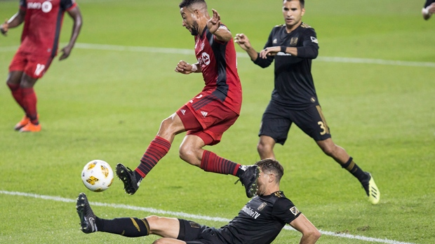 bb0b7901a88 Toronto FC's Justin Morrow has an attempt on goal despite the attentions of  Los Angeles FC's Dejan Jakovic during first half MLS action in Toronto on  ...