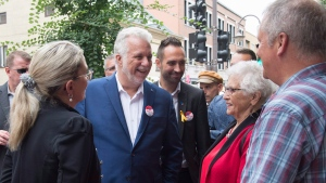 Quebec Liberal Leader Philippe Couillard, centre, his wife Suzanne Pilote, left, local candidate Florent Tanlet, centre right, chat with tourists while visiting the site of the Fete Arc-en-Ciel for LGBTQ, Saturday, September 1, 2018 in Quebec City. THE CANADIAN PRESS/Jacques Boissinot