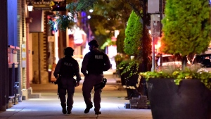 Tactical police officers walk along Danforth Avenue at the scene of a mass casualty incident in Toronto on Monday, July 23, 2018. THE CANADIAN PRESS/Frank Gunn