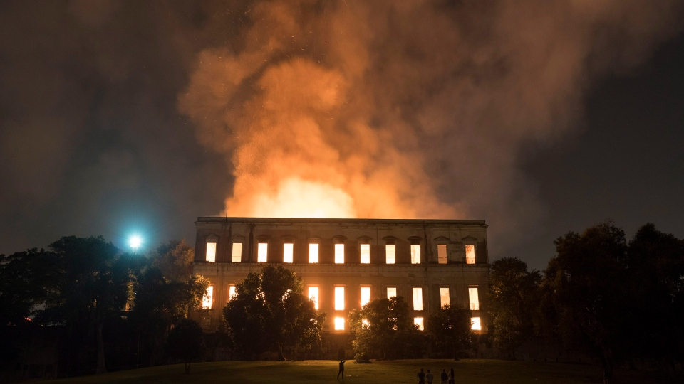 People watch as flames engulf the 200-year-old National Museum of Brazil, in Rio de Janeiro, Sunday, Sept. 2, 2018. (AP Photo/Leo Correa)