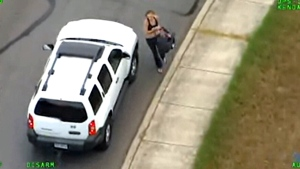 Video shot from a helicopter shows a woman leading Texas troopers on a high-speed chase and crashing into a pickup, then taking off on foot holding a baby in a carrier. (Texas Department of Public Safety)