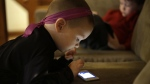 Nolan Young, 3, front, looks at a smart phone while his brother Jameson, right, 4, looks at a smart tablet at their home in Boston, on Jan. 27, 2014. (Steven Senne / AP)