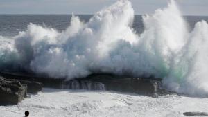A couple watches waves hitting a coast of Shirahara town, Wakayama prefecture, central Japan, Monday, Sept. 3, 2018. (Yosuke Mizuno/Kyodo News via AP)